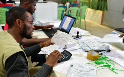 Members of Liberia's National Electoral Commission (NEC) check the results at the tally center in the capital Monrovia following the country's presidential and legislatives elections on October 12, 2017. The first official results from the presidential and legislative elections which took place on October 10, 2017, are expected from the National Elections Commission (NEC), which has already suggested that turnout was high for Liberia's first democratic transfer of power in seven decades. The vote is seen as a key test of the country's stability after the 12-year tenure of Ellen Johnson Sirleaf, Africa's first female president. / AFP PHOTO / ISSOUF SANOGO