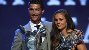 "Real Madrid's Portuguese forward Cristiano Ronaldo (L) poses the trophy after he was awarded the title of ""Best Men's Player in Europe"" while standing alongside "" Best Womans player in Europe"" Netherlands Lieke Martens at the conclusion of the UEFA Champions League group stage draw ceremony in Monaco on August 24, 2017. VALERY HACHE / AFP"