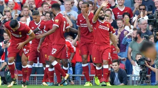 Liverpool's Egyptian midfielder Mohamed Salah (R) celebrates with teammates after scoring their third goal during the English Premier League football match between Liverpool and Arsenal at Anfield in Liverpool, north west England on August 27, 2017. Anthony Devlin / AFP