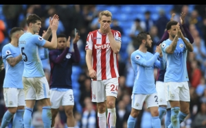 Stoke City's Scottish midfielder Darren Fletcher reacts as Manchester City players celebrate their victory at the end of the English Premier League football match between Manchester City and Stoke City at the Etihad Stadium in Manchester, north west England, on October 14, 2017. / AFP PHOTO / Lindsey PARNABY