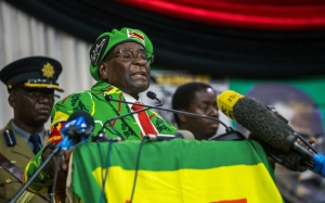 Zimbabwe's President Robert Mugabe delivers a speech during a meeting of his party's youth league where he hinted at a cabinet reshuffle, on October 7, 2017, in Harare. Robert Mugabe warned some ministers will be axed in a shake-up of his cabinet amid deepening infighting in his Zanu-PF party over who succeeds him. Mugabe's announcement came amid escalating tension between rival factions jostling to succeed the 93-year-old — including his lieutenants and his wife. / AFP PHOTO / Jekesai NJIKIZANA