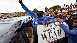 Former international Liberian football star turned politician George Weah, greets his supporters during a campaign rally in Monrovia on October 8, 2017, three days ahead of the country's elections. Liberians go to the polls on October 10, to pick their first new president in 12 years as Ellen Johnson Sirleaf closes the page on two terms dominated by post-war reconstruction and the Ebola crisis. ISSOUF SANOGO / AFP
